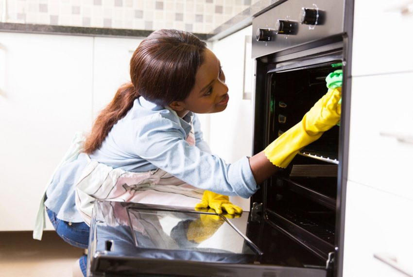 woman cleaning an oven